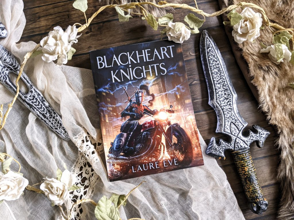 Blackheart Knights book shown next to two daggers and flowers